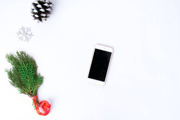 Smartphone cell phone with christmas decoration, silver ribbon, branch of pane, silver snowflake, snow cone, new year stock photo