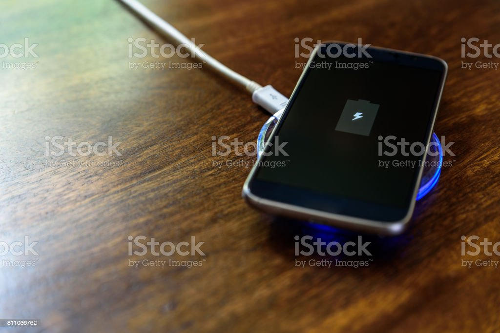 Smartphone charging on a charging pad. Wireless charging stock photo