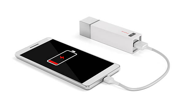 Smartphone charging with external battery Smartphone charging with power bank on white background battery charger stock pictures, royalty-free photos & images