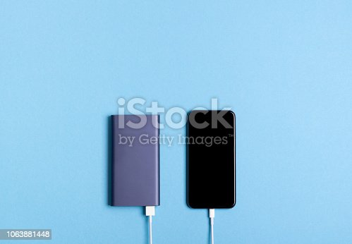 Smartphone charging with power bank on blue background