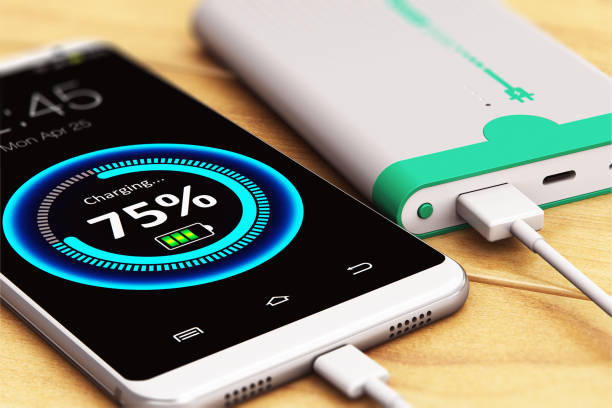 Smartphone charging with power bank 3D render illustration of the macro view of smartphone or mobile phone charging by a portable power bank rechargeable battery pack on the wooden table with selective focus effect battery charger stock pictures, royalty-free photos & images