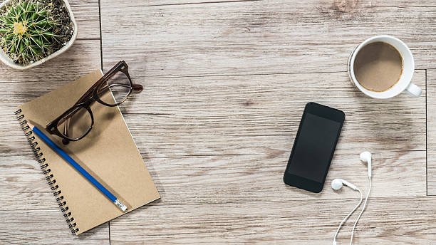 Smartphone, earphones, notebook and coffee on wooden background stock photo