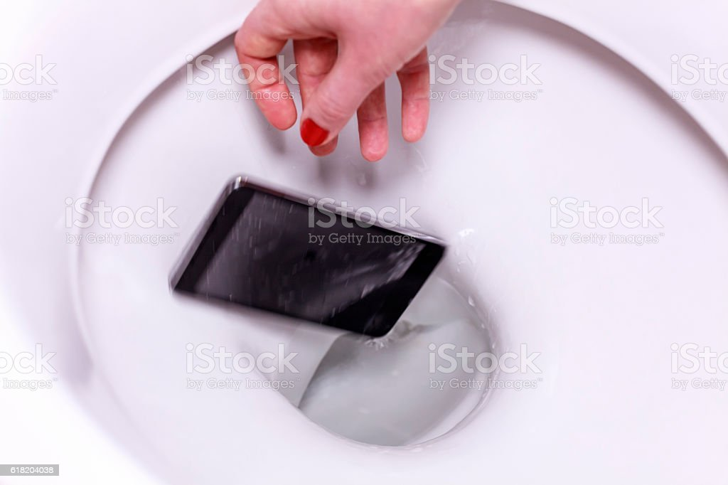 Smartphone Fallen into the Toilet Bowl stock photo