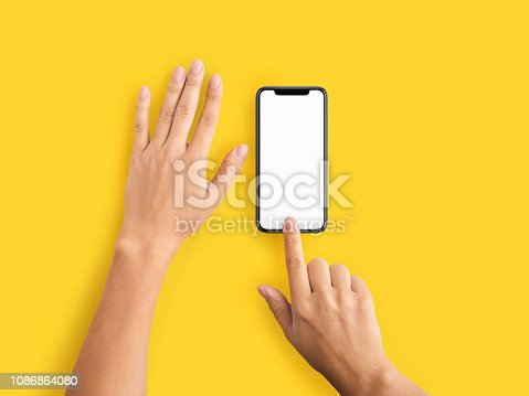 Smartphone finger scan security and privacy protection. Hand using mobile phone with blank screen on yellow background, copy space