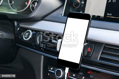 istock Smartphone in a car use for Navigate or GPS. Driving a car with Smartphone in holder. Mobile phone with isolatede white screen. Blank empty screen. copy space. Empty space for text. modern car interior details. 843550748