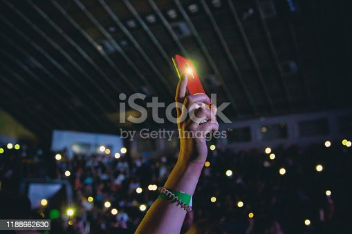 Smartphone with a turned on flashlight in a female hand at a concert.