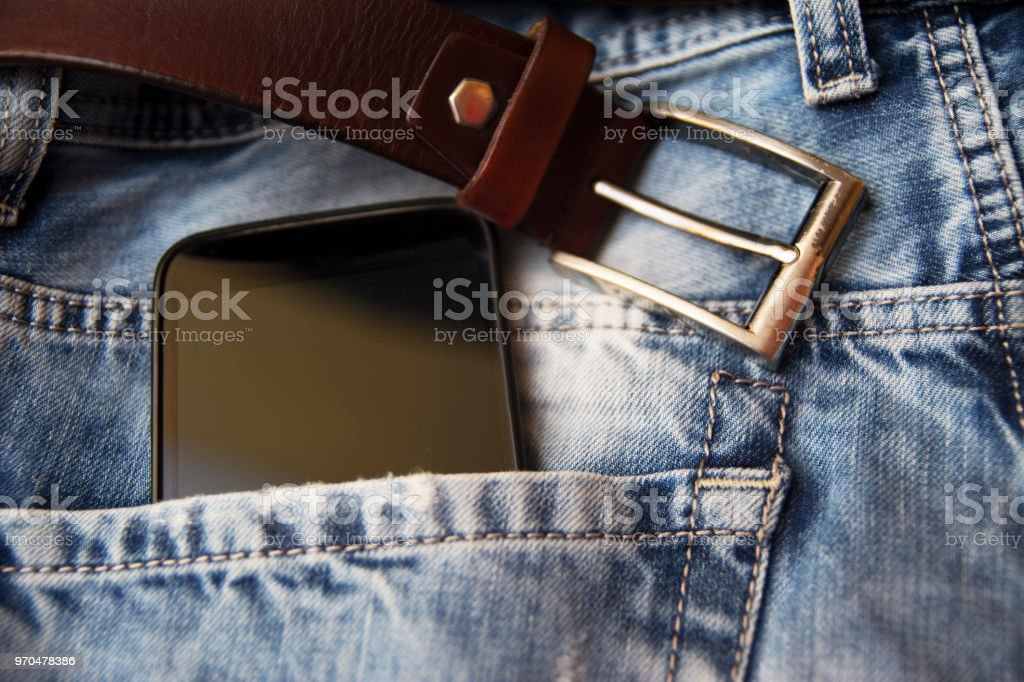 Smartphone in back pocket of jeans pants stock photo
