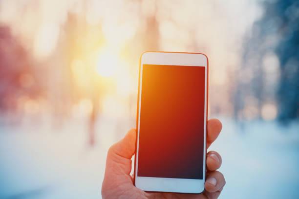 teléfono inteligente en mano en el bosque en invierno. imagen de maqueta. hombres que muestran teléfono inteligente al aire libre - foto de stock