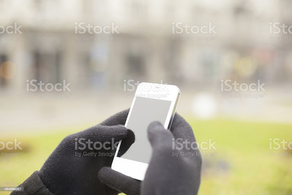 Smartphone in hand with gloves stock photo
