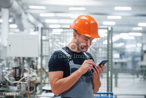 Smartphone in hands. Industrial worker indoors in factory. Young technician with orange hard hat.