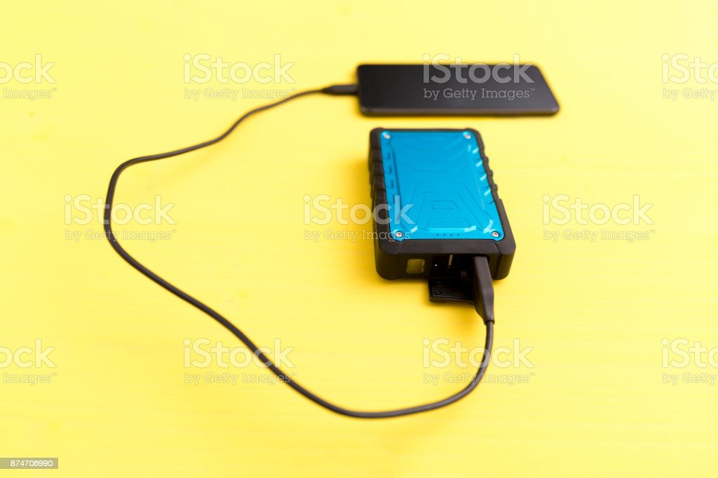 Smartphone is charged from the portable power bank, battery stock photo