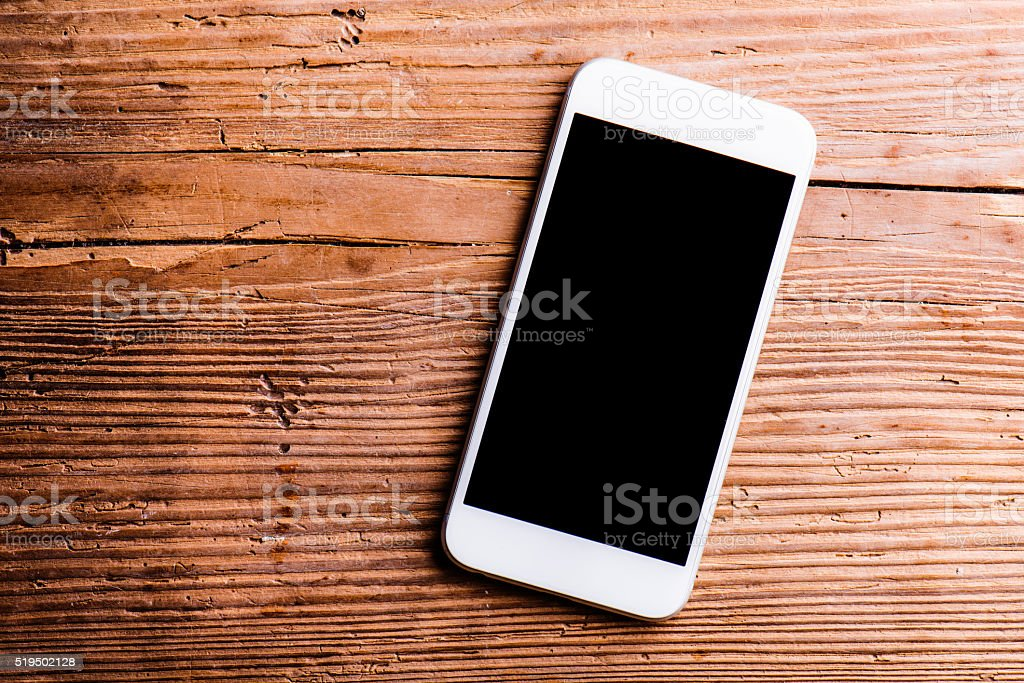 Smartphone laid on an old office desk, copy space stock photo