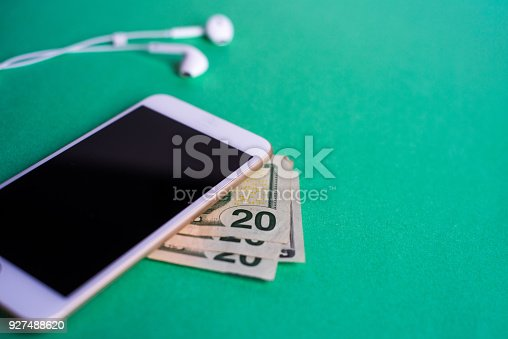 A smartphone with headphones on a green background