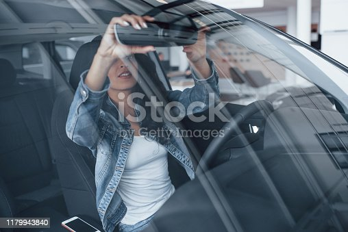 Smartphone lying down. Cute girl with black hair trying her brand new expensive car in the automobile salon.