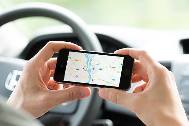 Smartphone mapping while in car Kiev, Ukraine - May 16, 2014: Man in the car planning a route using a Google Maps application on Apple iPhone 5S. Google Maps is a most popular web mapping service for mobile provided by Google inc. google stock pictures, royalty-free photos & images