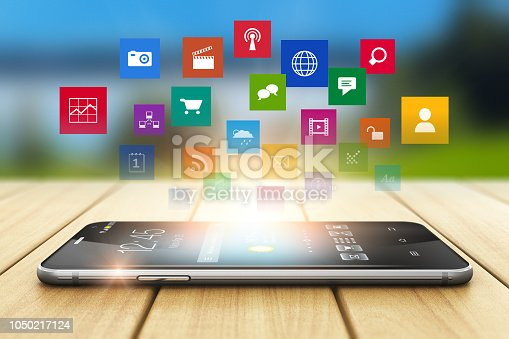 Creative abstract wireless media technology business communication internet web concept: 3D render illustration of the modern black glossy touchscreen smartphone with group of color app or application software program icons on wooden plank table outdoors with selective focus bokeh blur effect