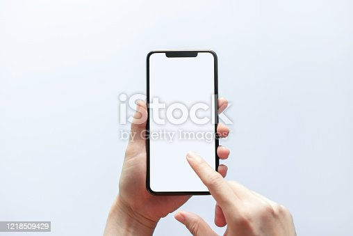 1084491176 istock photo Smartphone mockup. Hand holding black phone white screen. Isolated on white background. Mobile phone frameless design concept. 1218509429