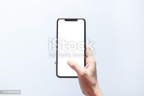 1084491176 istock photo Smartphone mockup. Hand holding black phone white screen. Isolated on white background. Mobile phone frameless design concept. 1218938495