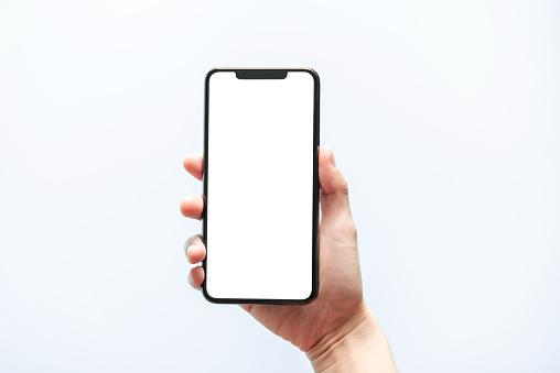 Smartphone mockup. Hand holding black phone white screen. Isolated on white background. Mobile phone frameless design concept.