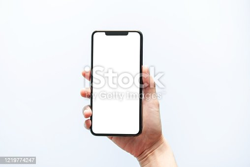 1084491176 istock photo Smartphone mockup. Hand holding black phone white screen. Isolated on white background. Mobile phone frameless design concept. 1219774247