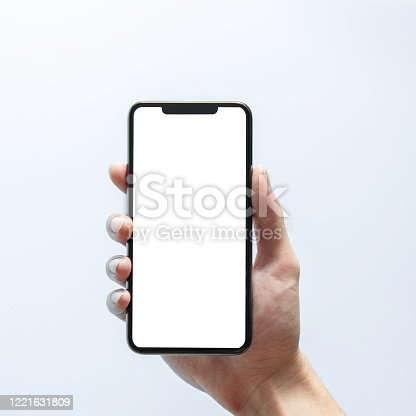 1084491176 istock photo Smartphone mockup. Hand holding black phone white screen. Isolated on white background. Mobile phone frameless design concept. 1221631809