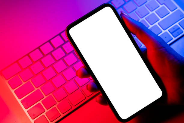 Smartphone mockup in woman hand in blue and pink tones. Frameless smartphone mock up with blank white screen. Empty space for text. Copy space. Isolated white screen with clipping path stock photo