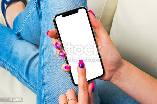 istock Smartphone mockup in woman hand. New modern black frameless smartphone mock up with blank white screen. Empty space for text. Copy space. Isolated white blank screen. 1124510556