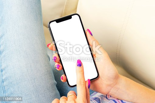 istock Smartphone mockup in woman hand. New modern black frameless smartphone mock up with blank white screen. Empty space for text. Copy space. Isolated white blank screen. 1124511904