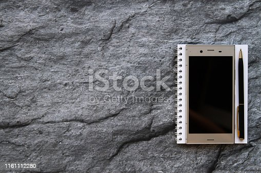 smartphone notebook and paper wordpad on stone background with copy space