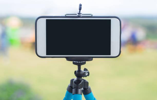 smartphone on a tripod  with tree backdrop with sky and clouds - statyw zdjęcia i obrazy z banku zdjęć