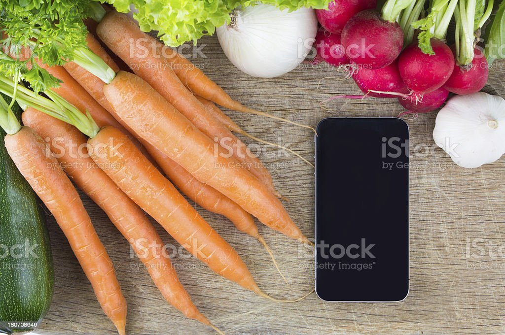 Smartphone on cutting board with fresh vegetables royalty-free stock photo