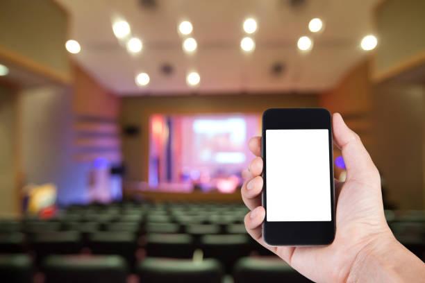 Smartphone auf Hand und weißen Bildschirm mit unscharfen Hintergrund des Theaters. – Foto