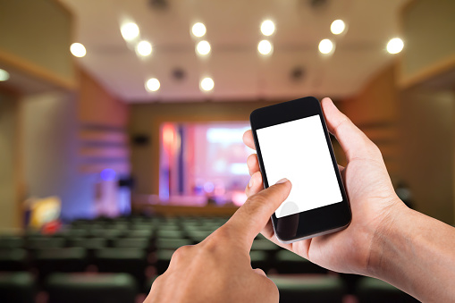 Smartphone on hand and white screen with blurry background of theater.
