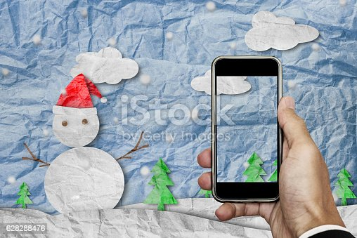 527392693 istock photo Smartphone on hand with blank screen, Christmas crumpled paper cut 628288476