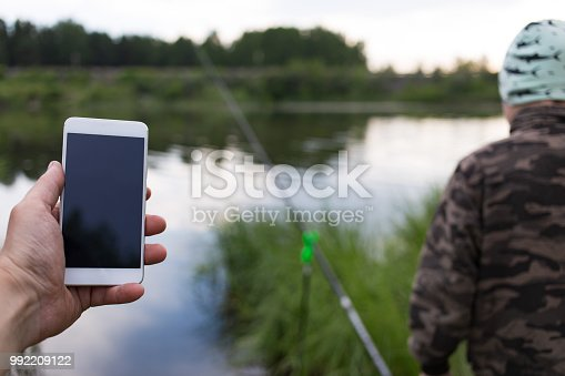 istock Smartphone on the background lakes and fishing rods 992209122
