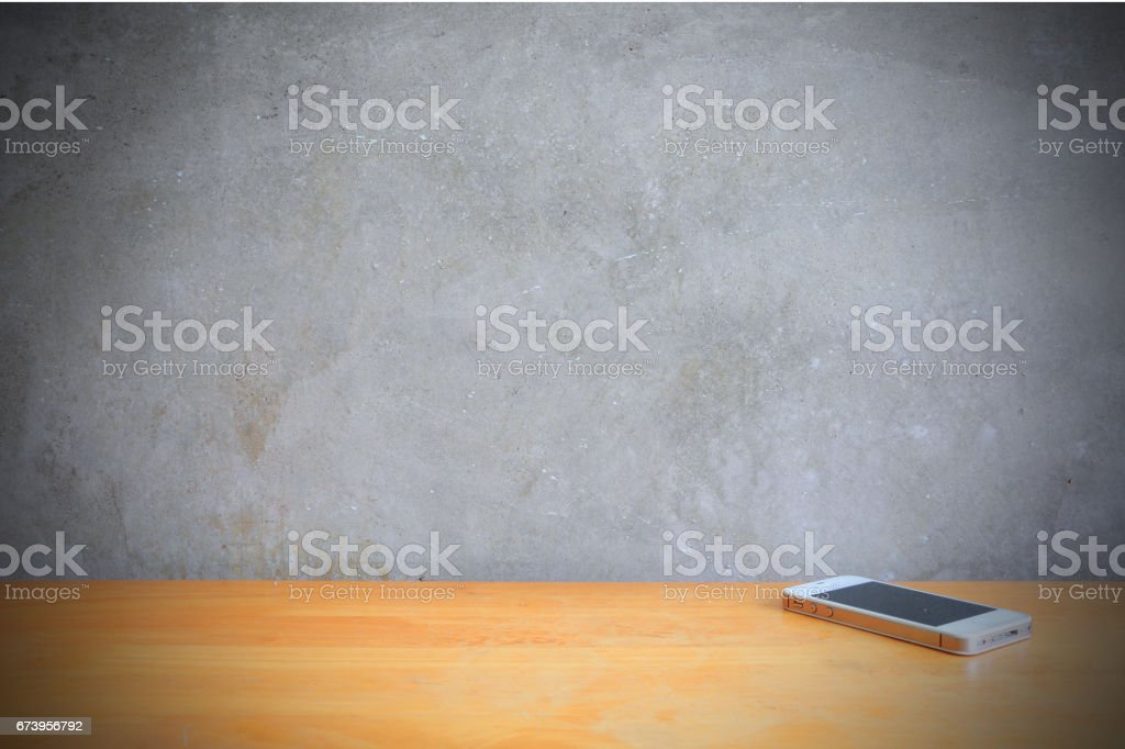 Smartphone on the table in front of cement wall royalty-free stock photo