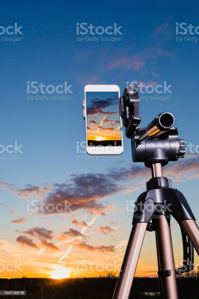 Smartphone on tripod capturing image of sundown in vertical mode stock photo