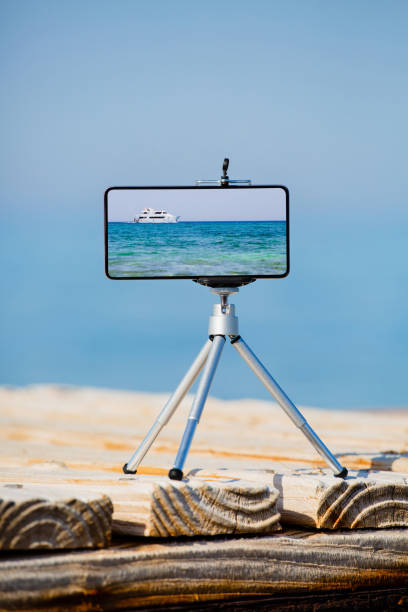Smartphone on tripod making photo and video of sea landscape stock photo