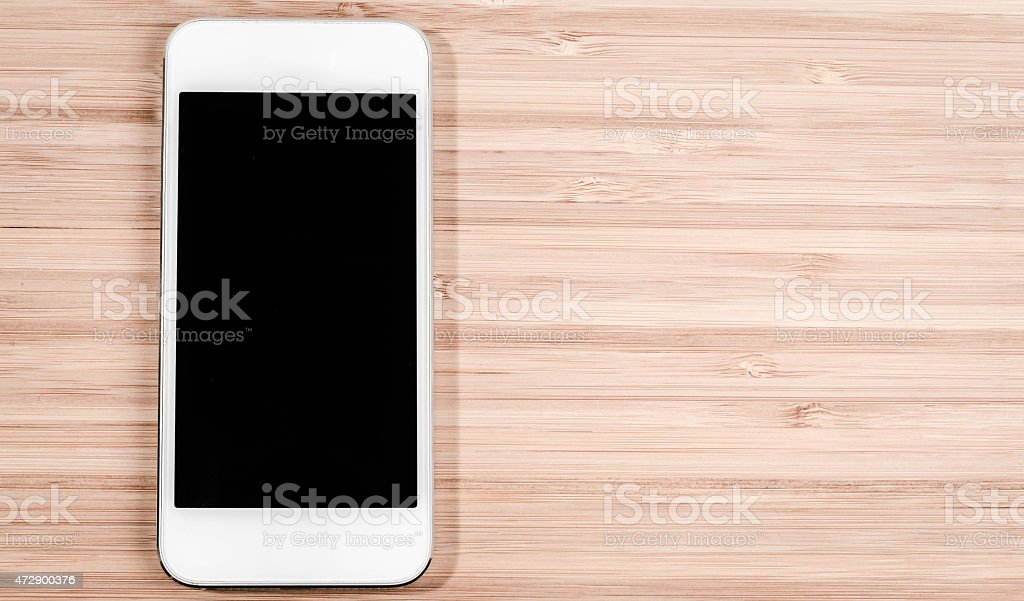 Smartphone on wooden table stock photo