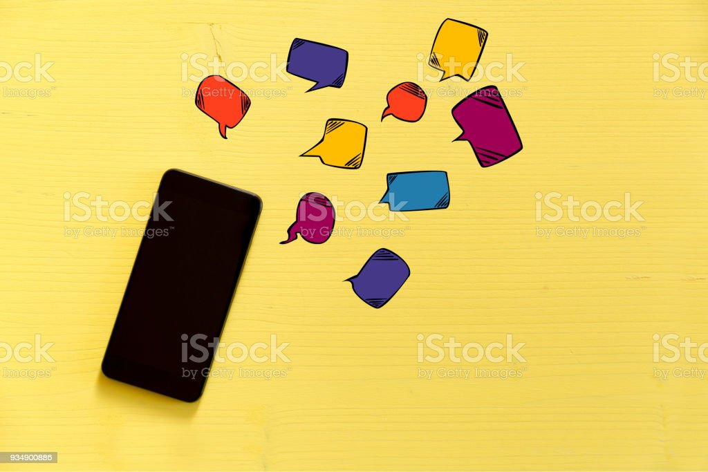 Smartphone on yellow background with text bubbles around. Messaging, texting and connection concept stock photo