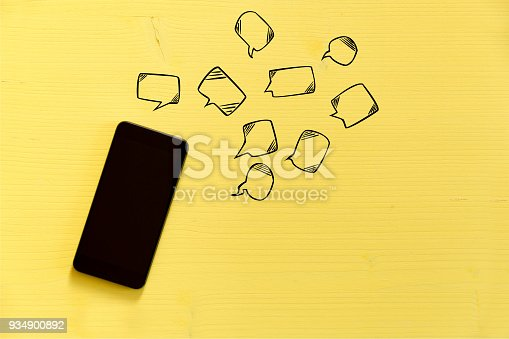 istock Smartphone on yellow background with text bubbles around. Messaging, texting and connection concept 934900892