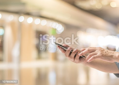 693192954 istock photo Smartphone online shopping concept with woman's hands using mobile smart phone device with internet technology for digital city lifestyle in blur shopping mall 1079938052