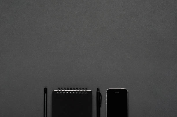 Smartphone, pen, pencil stationery on a dark gray background. Office desktop. Copy space, top view, flat lay. stock photo