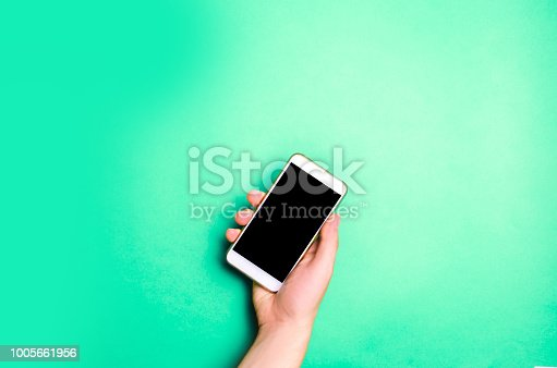 istock smartphone, phone in male hands on a green background. the concept of communication. use of gadgets, modern technologies. social networks. place for text. copyspace 1005661956