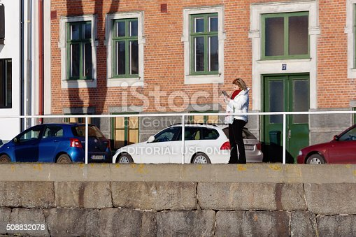 Karlshamn, Sweden - February 04, 2016: An unknown female is using her mobile phone to take photographs as she stand outside a building close to a railing.