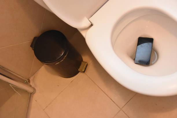 smartphone opgeslagen op het laatste moment - cell phone toilet stockfoto's en -beelden