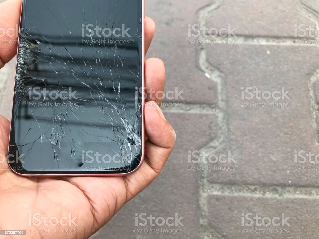 Smartphone screens break in the hand from falling ground and space agreement stock photo