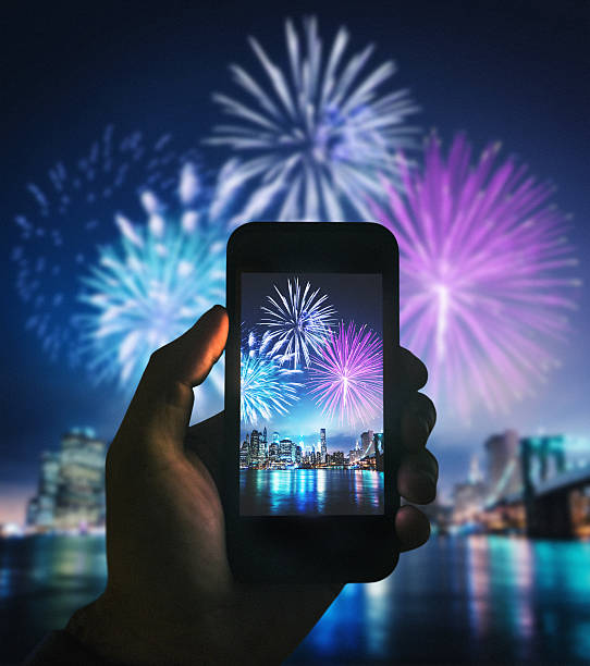smartphone take a pic of the nyc celebration smartphone take a pic of the nyc celebration fireworks photos stock pictures, royalty-free photos & images