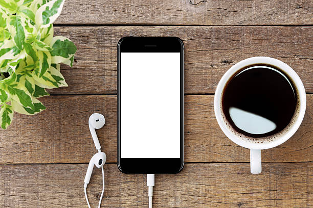 smartphone white screen on wooden table smartphone white screen on wooden table, mockup modern smartphone jet black color overhead projector stock pictures, royalty-free photos & images