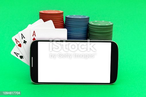 istock Smartphone with blank screen, poker chips and playing cards on green background. Online poker. Space for text. 1094617704